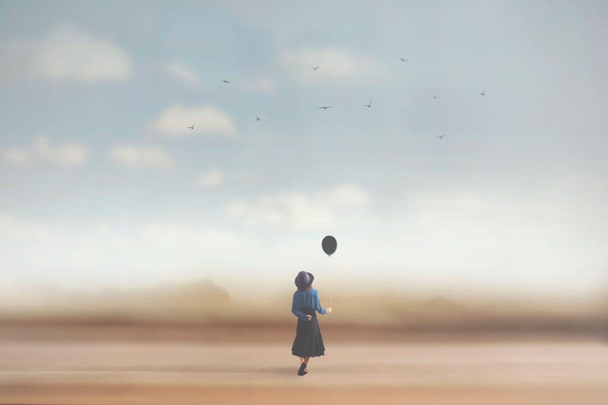 Woman on Beach Holding a Balloon