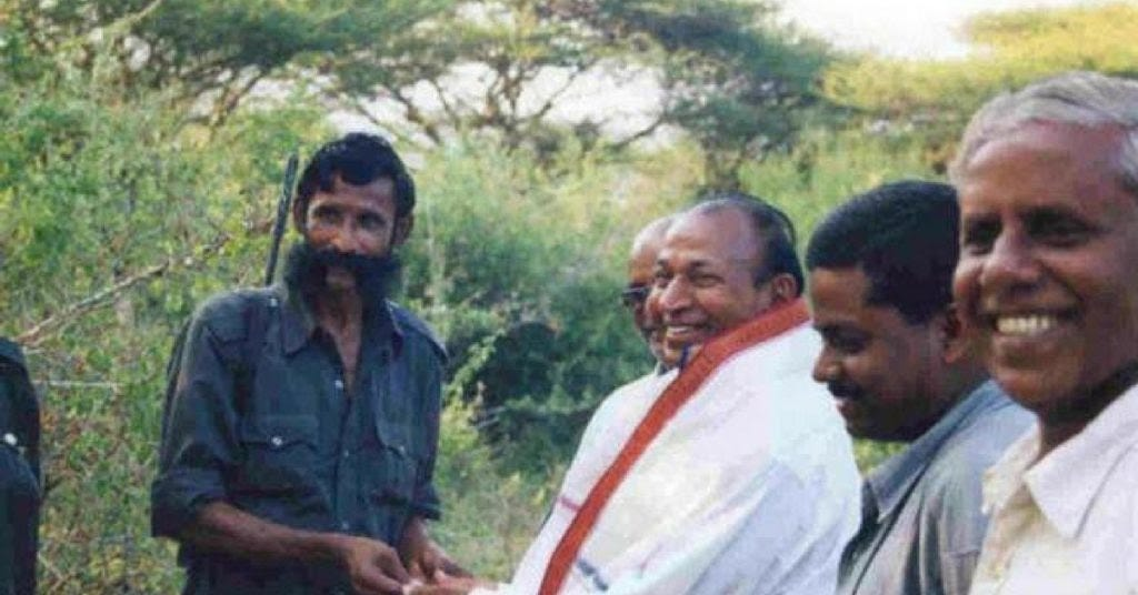 A photograph of the bandit Veerappan clasping hands with the actor Rajkumar, both men are smiling and Veerappan's moustache bristles.