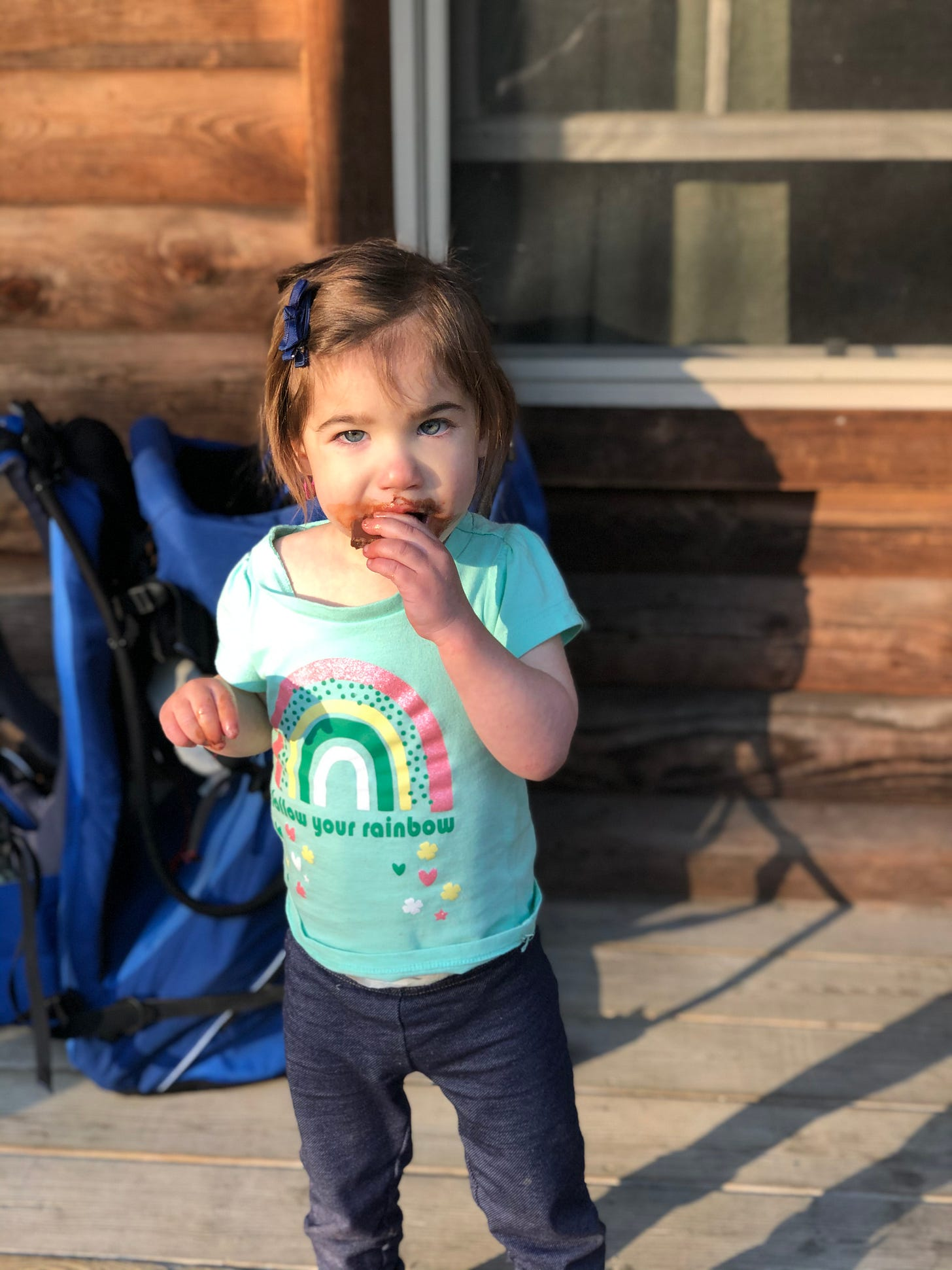 Photograph of Lila eating a chocolate bar with her face covered in chocolate.