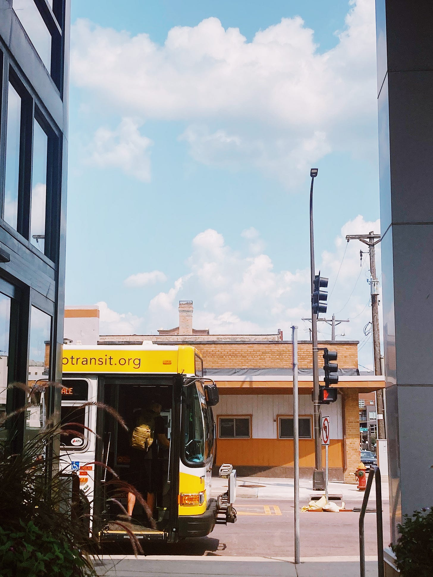 a passenger climbs onto a metro transit bus in front of a brick building and blue sky with white clouds