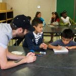 An Austin Bat Cave volunteer working with two elementary school students to write together at a black table in a classroom of other students in the background.