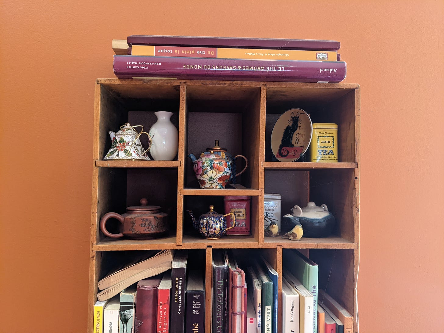 Wooden bookshelf with compartments for tea and shelves for books against orange wall.