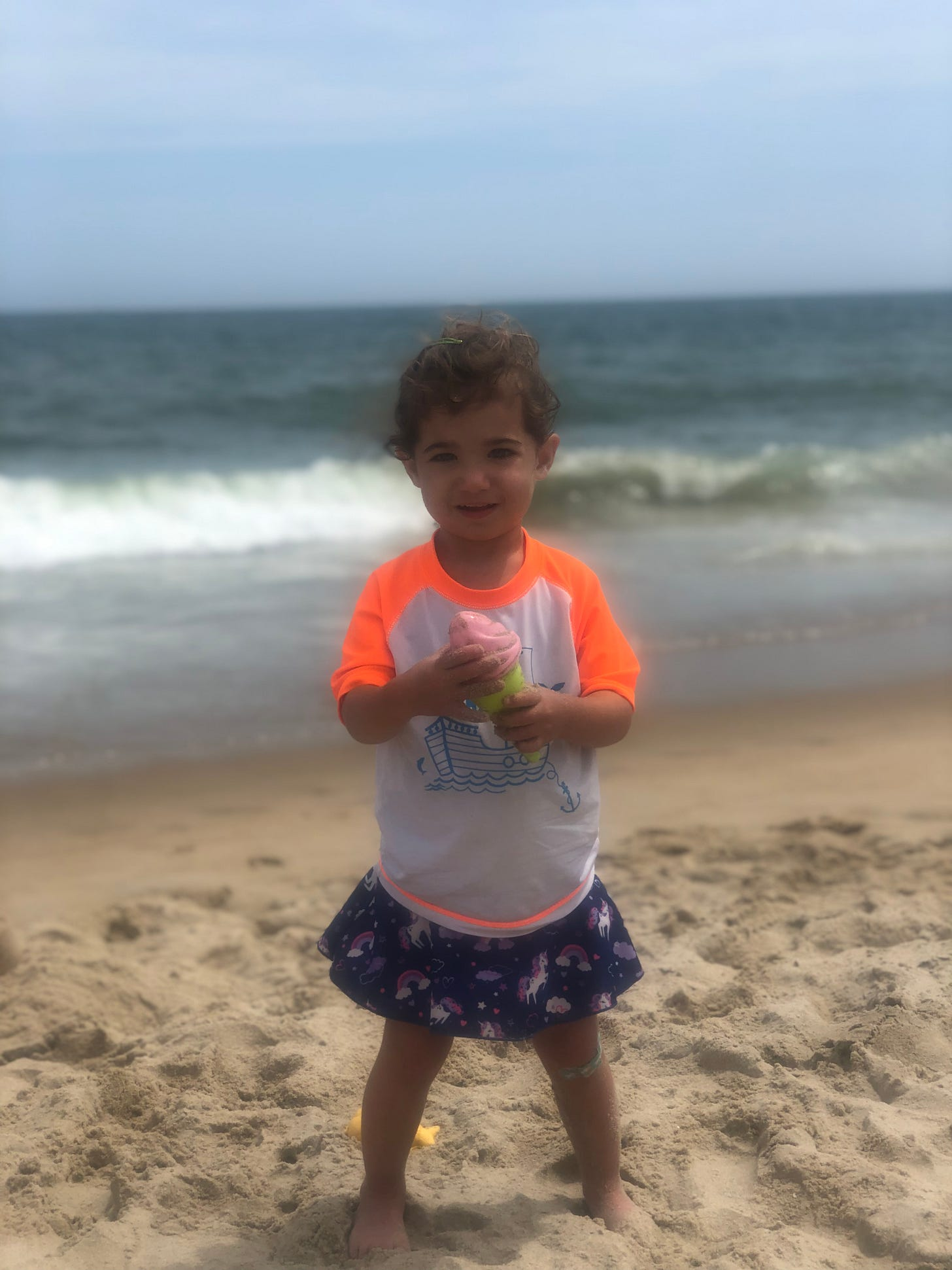 Photo of Lila with the ocean behind her.