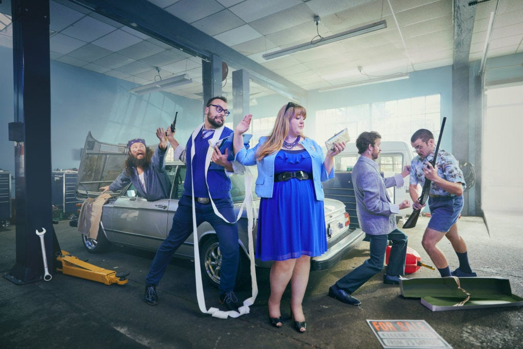 Group shot of J Names Improv comedy in a mechanics garage