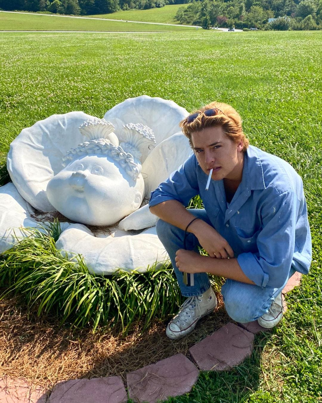 Cole Sprouse, dressed in all denim, kneels beside a stone statue of a Cabbage Patch Kid mid-birth, cigarette perched on the edge of his lips.