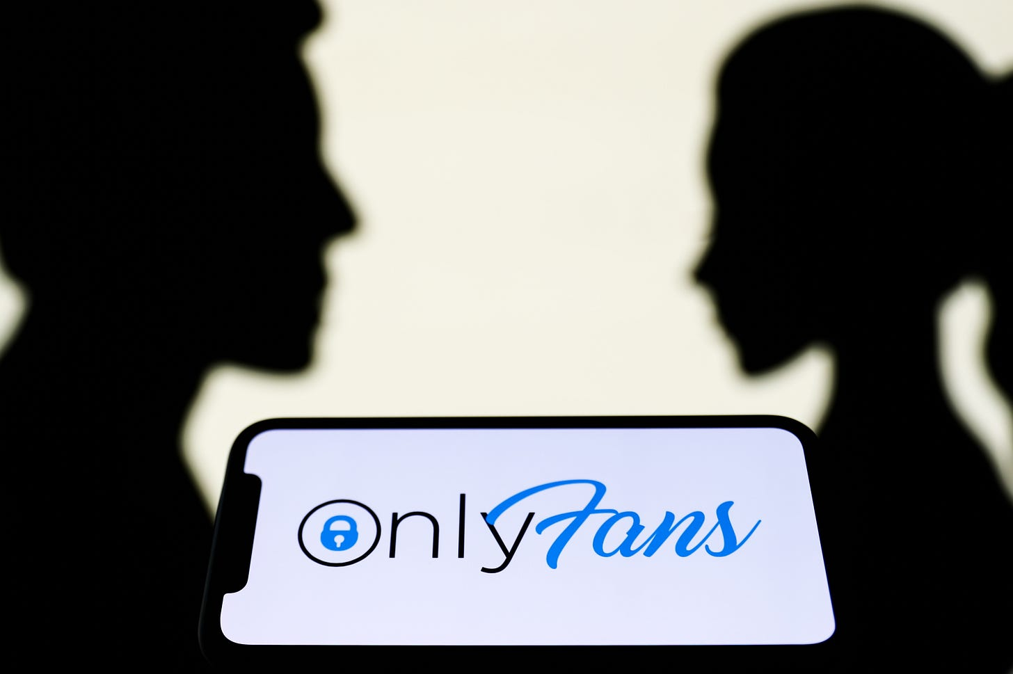 OnlyFans logo displayed on a phone screen is seen with paper silhouettes looking like a man and a woman in the background in this illustration photo taken in Krakow, Poland on August 25, 2021. (Photo by Jakub Porzycki/NurPhoto via Getty Images)