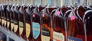 bottles of barrell bourbon lined up on the shelf
