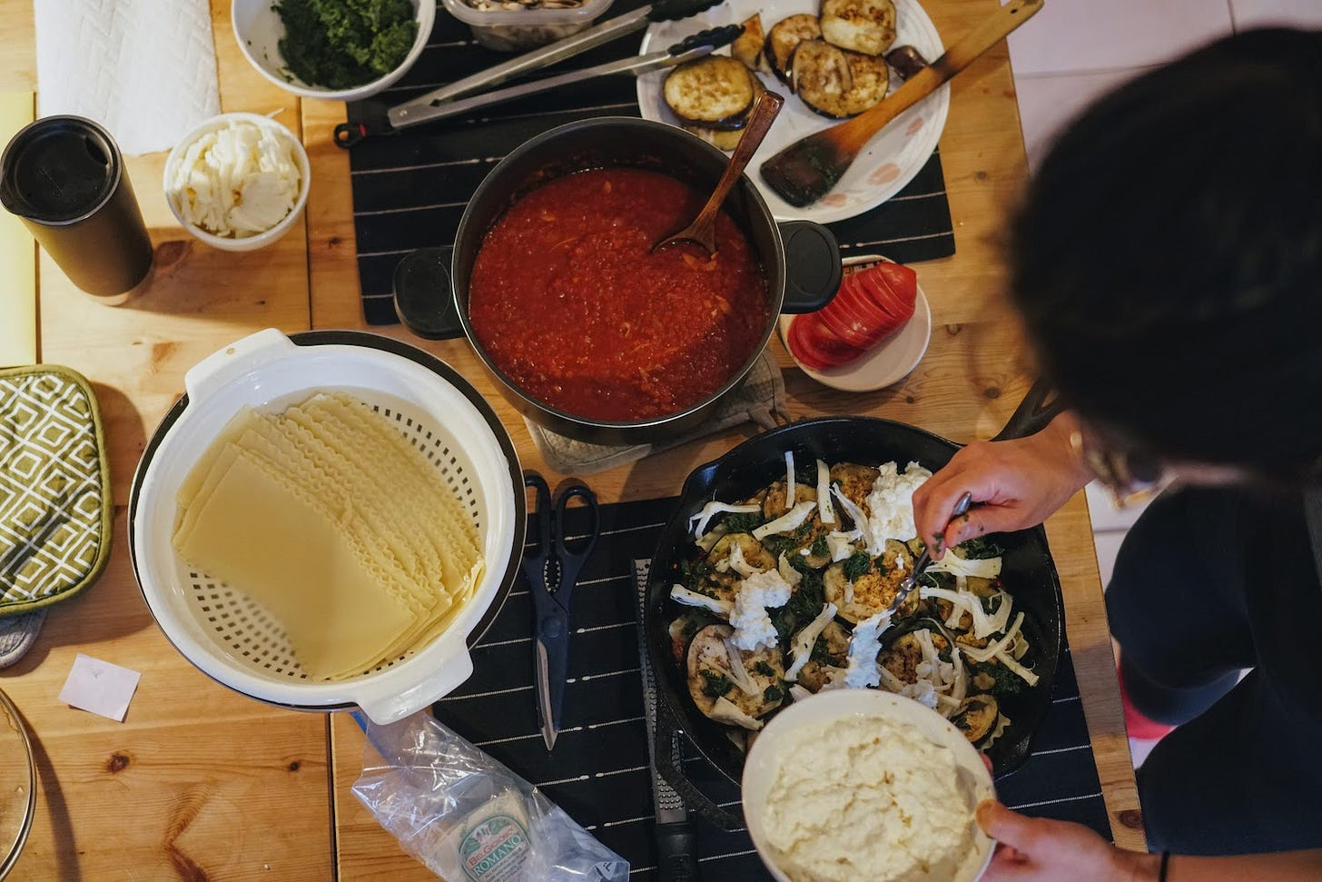 Ingredients for lasagna being assembled in a cast iron