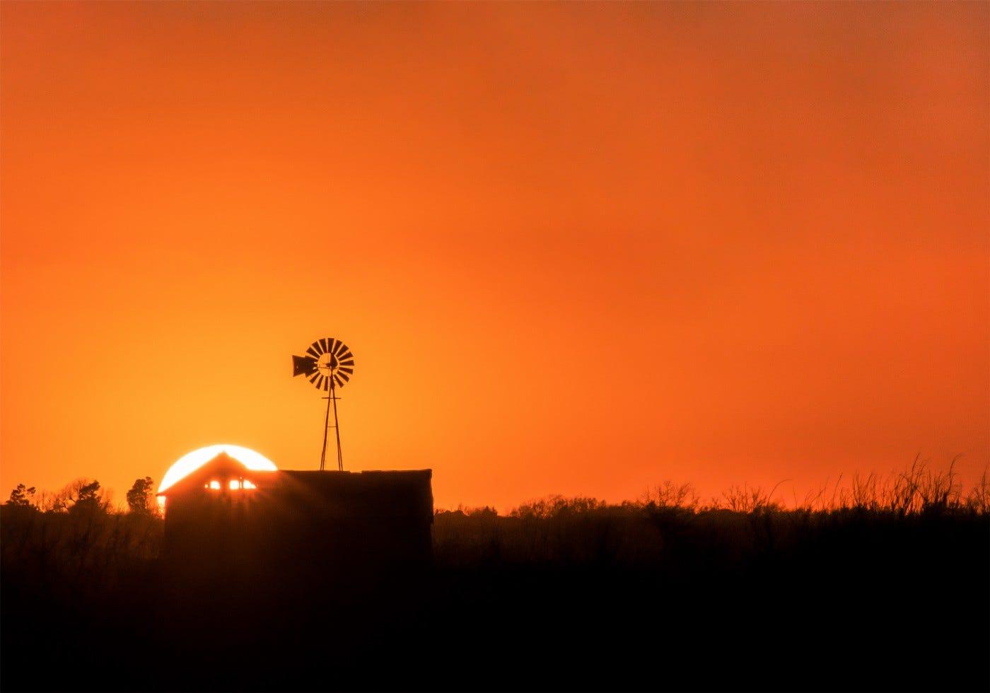The sun setting behind a barn