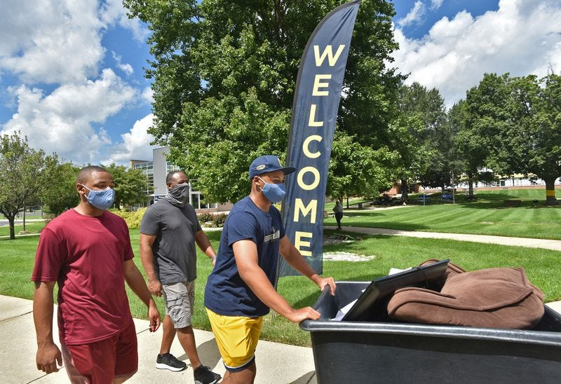 Toran Smith, 19, a returning second-year student at Coppin State University, pushes a cart with his belongings toward his dorm, accompanied by his brother Cameron, left, and father, Sam Smith behind them. They drove to campus from Plainfield, New Jersey. Aug. 23, 2020. (Amy Davis/Baltimore Sun)