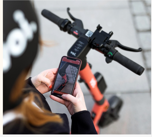 A girl with a helmet is looking at an app on her phone.