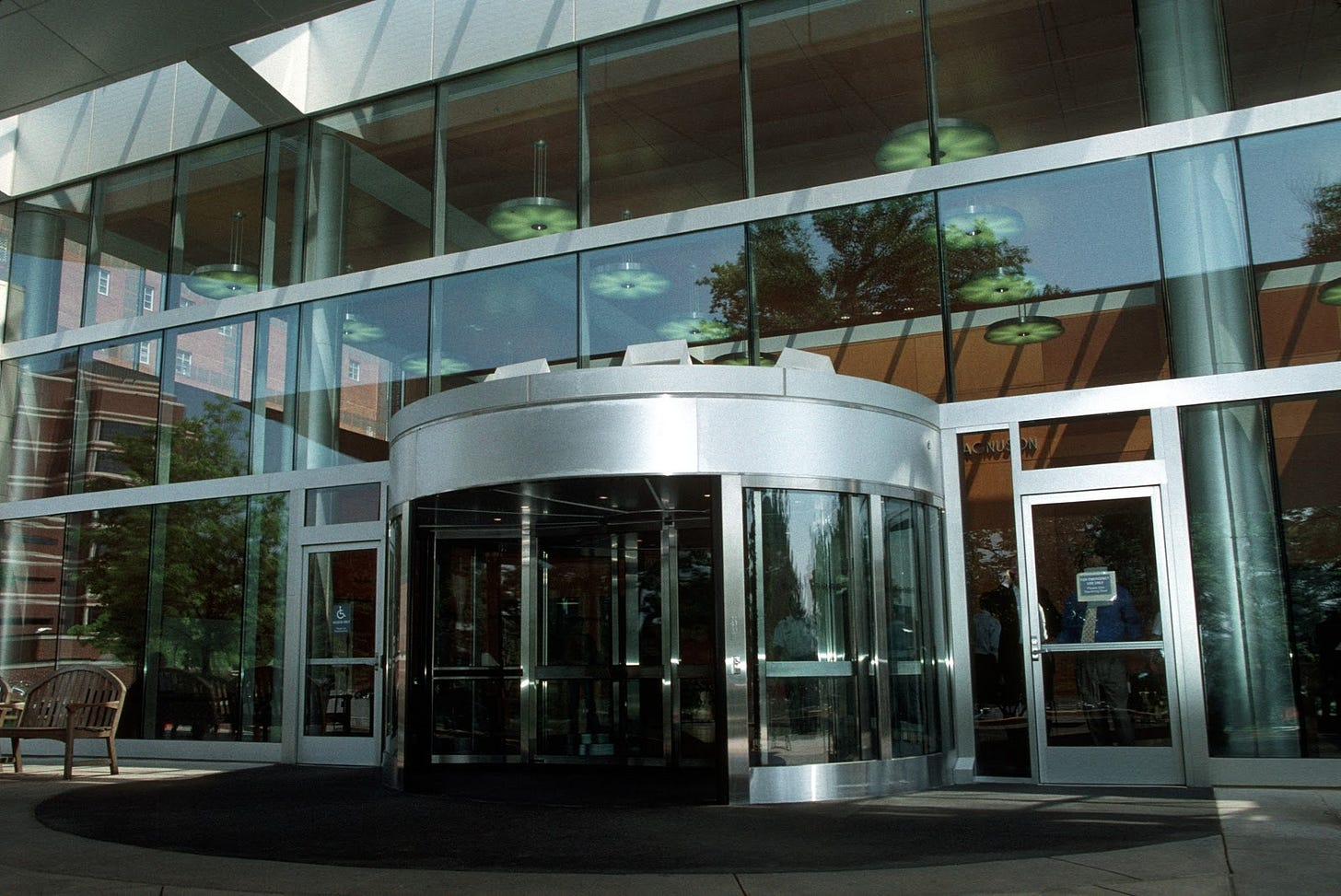 Wide shot of a revolving door at an office building. Image via Unsplash.