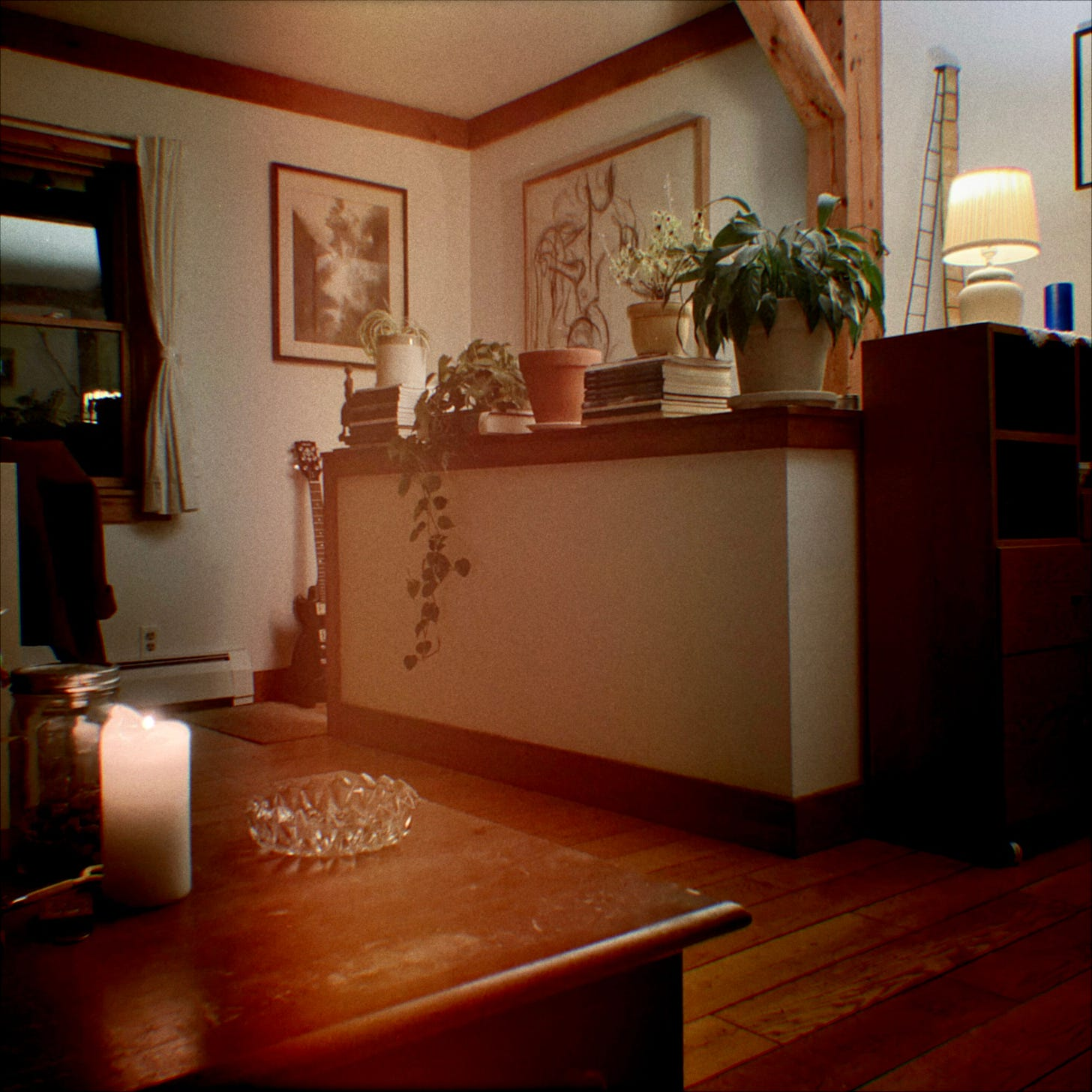 A snapshot of a lounge area with a sepia hue. In the lower right corner is a dark brown wooden table with a lit white candle and a cut glass bowl on it. Further to the right are windows with open curtains. In the centre, there is a high white ledge with several plants on it, behind there are two paintings on the white walls. To the top left is a lit small white lamp on another dark wooden piece of furniture.