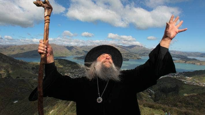 A picture of an extremely wizardly looking gent; black robe and hat, long gray beard, wizard's staff etc, holding up his hand spellcaster-style in front of a dramatic New Zealand landscape.