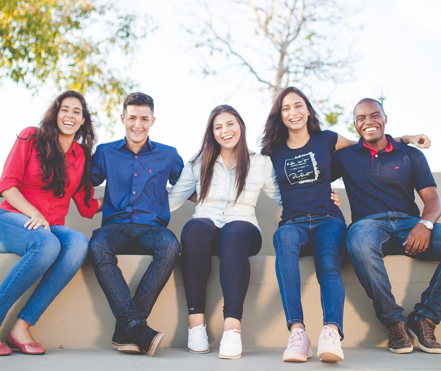 Image of a diverse group of five smiling friends sitting side-by-side on a sunny day with their arms around each other.