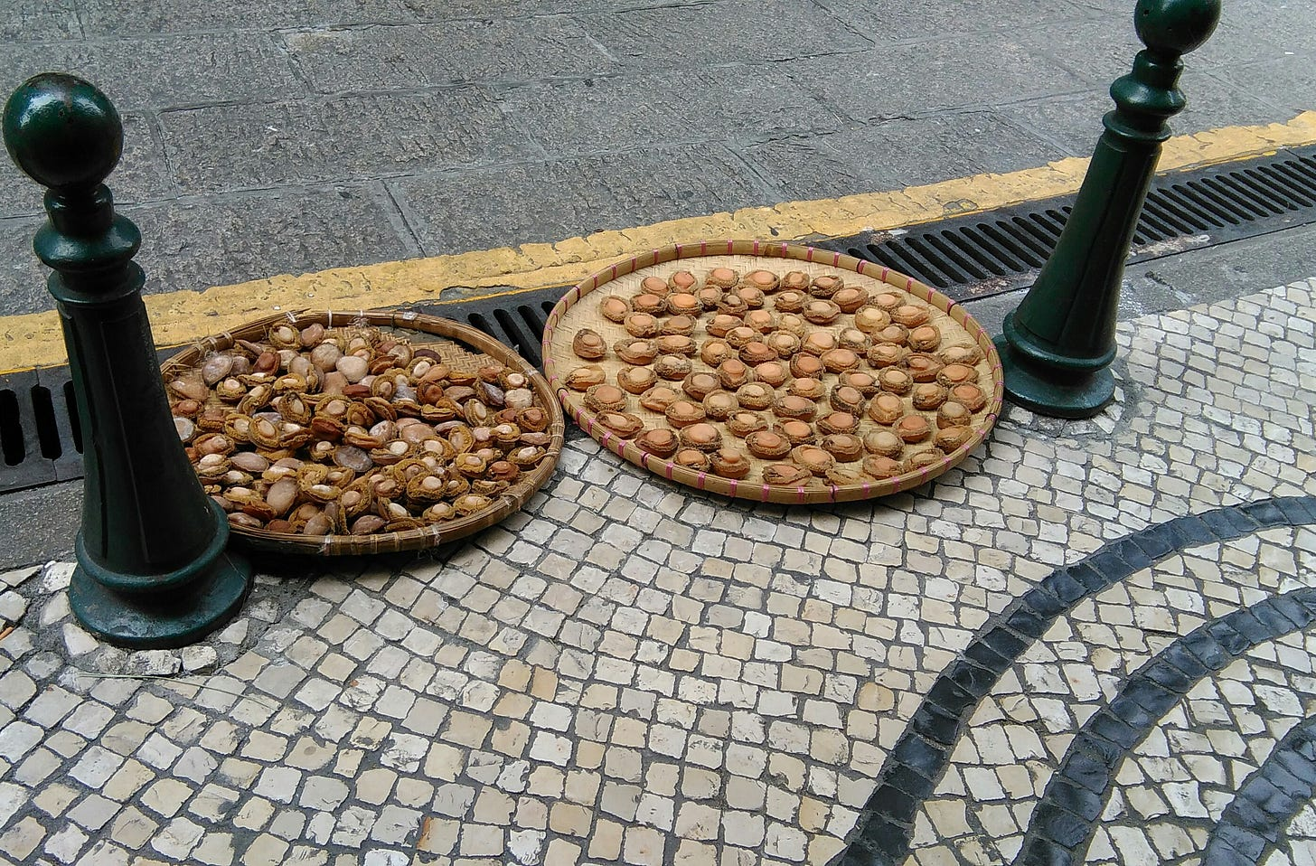 A shot of a pavement in Macau where abalone are drying on large round wicker baskets