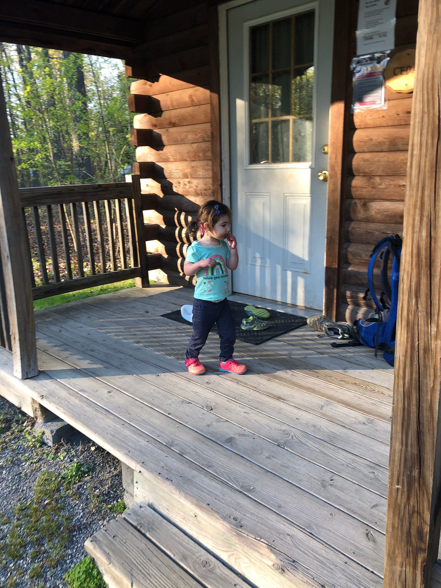Photograph of a toddler wandering on a wooden porch in front of a log cabin.