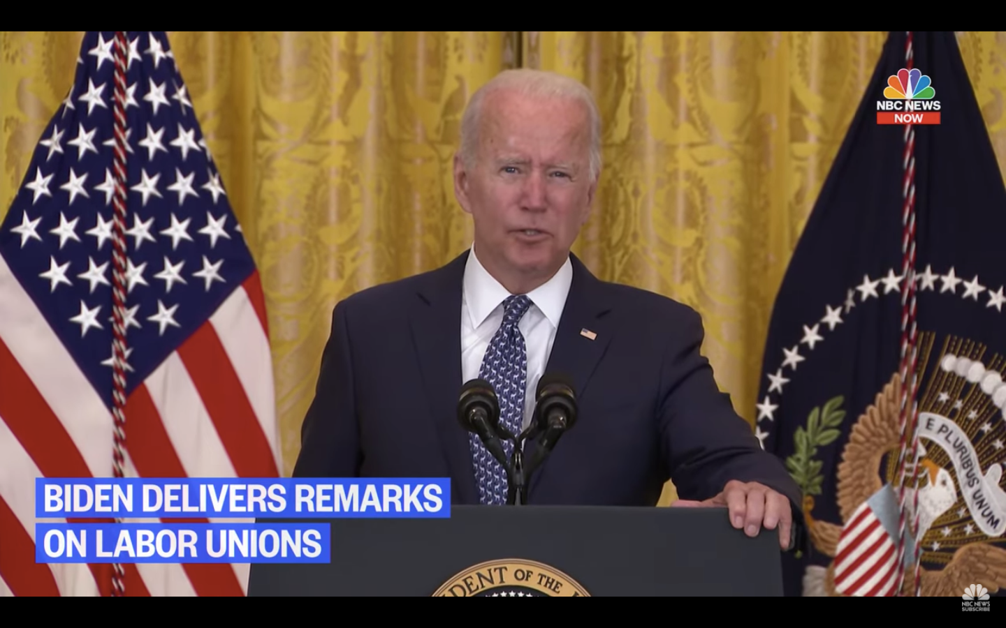 a screenshot of Joe Biden at a presidential podium in front of a US flag and Washington, D.C., flag speaking into a microphone