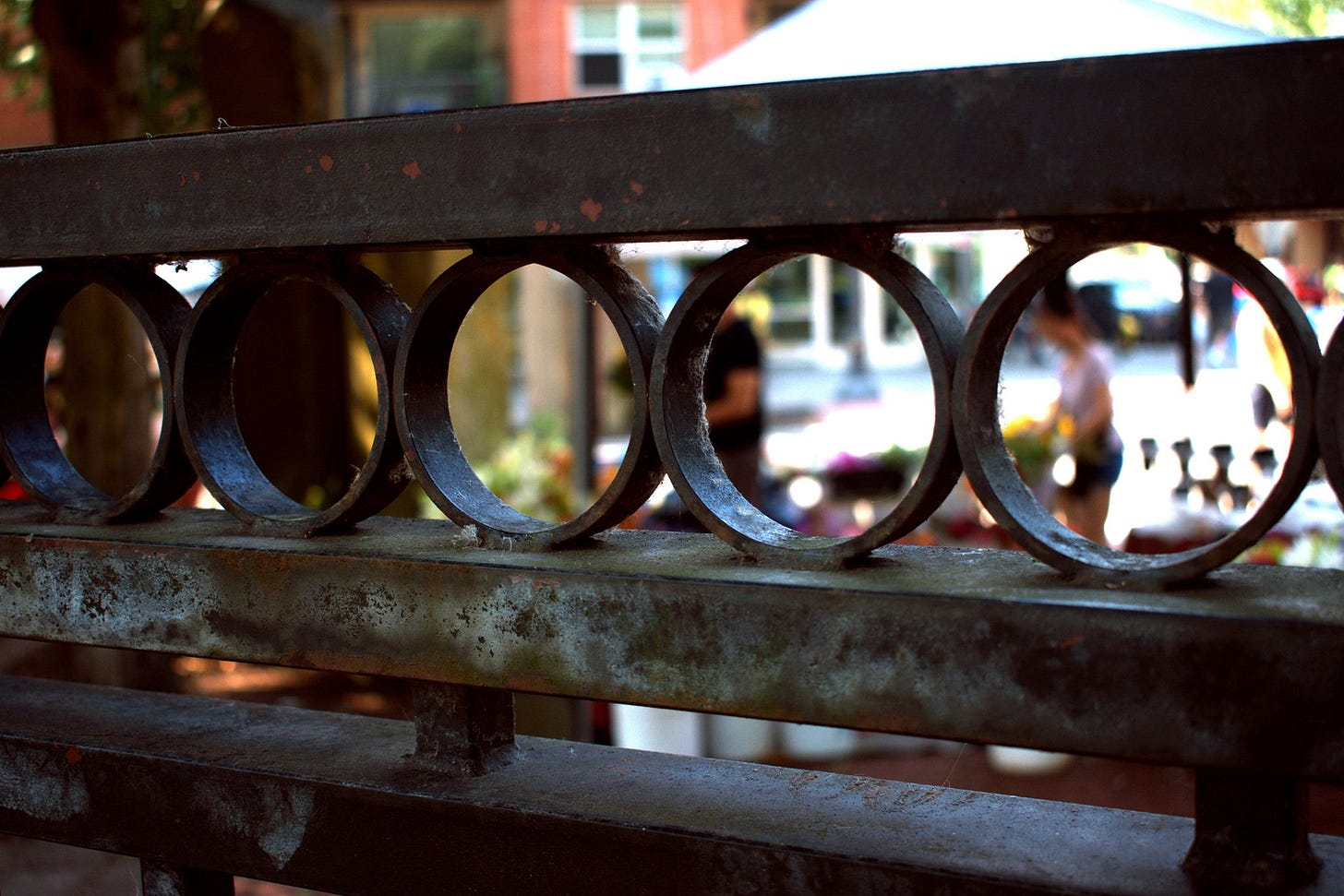 Photograph of an old gate, through which we see people at Vancouver Farmer's Market buying colorful flowers.