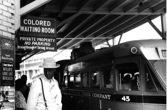 """Photo at a railroad station with a sign that reads """"colored waiting room"""""""