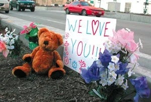 Artificial flowers and a $7.99 teddy bear adorn the site of the tragedy.