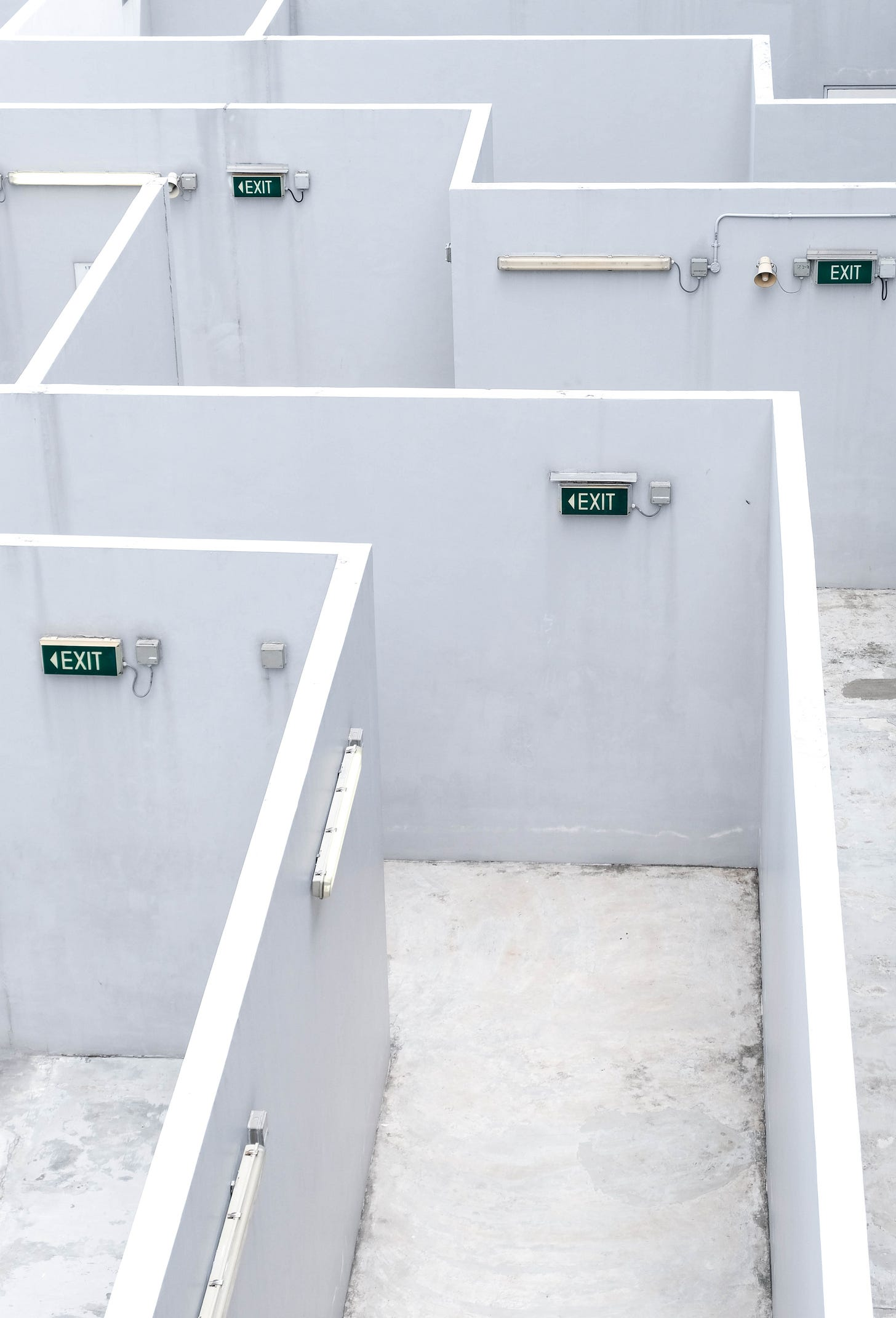 Photo of a maze with white walls and several green exit signs
