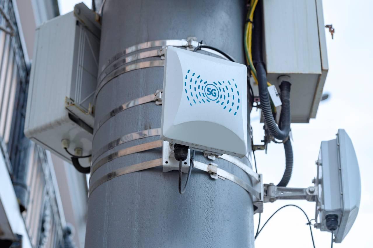 Placa indicando sinal 5G em poste de energia