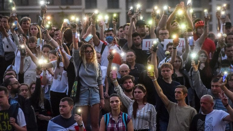 TOPSHOT - Belarus opposition supporters raise their mobile phones with flashlights during a symbolic minute of silence near the State TV and radio company during a protest rally against police violence recent rallies of opposition supporters, who accuse strongman Alexander Lukashenko of falsifying the polls in the presidential election, in central Minsk on August 15, 2020. (Photo by Sergei GAPON / AFP) (Photo by SERGEI GAPON/AFP via Getty Images)