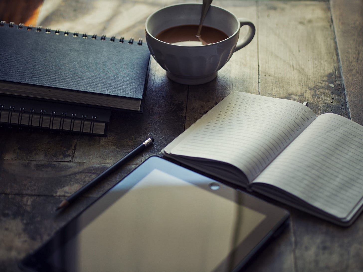 Image of a coffee cup, writing pad and tablet on a table for article by Larry G. Maguire