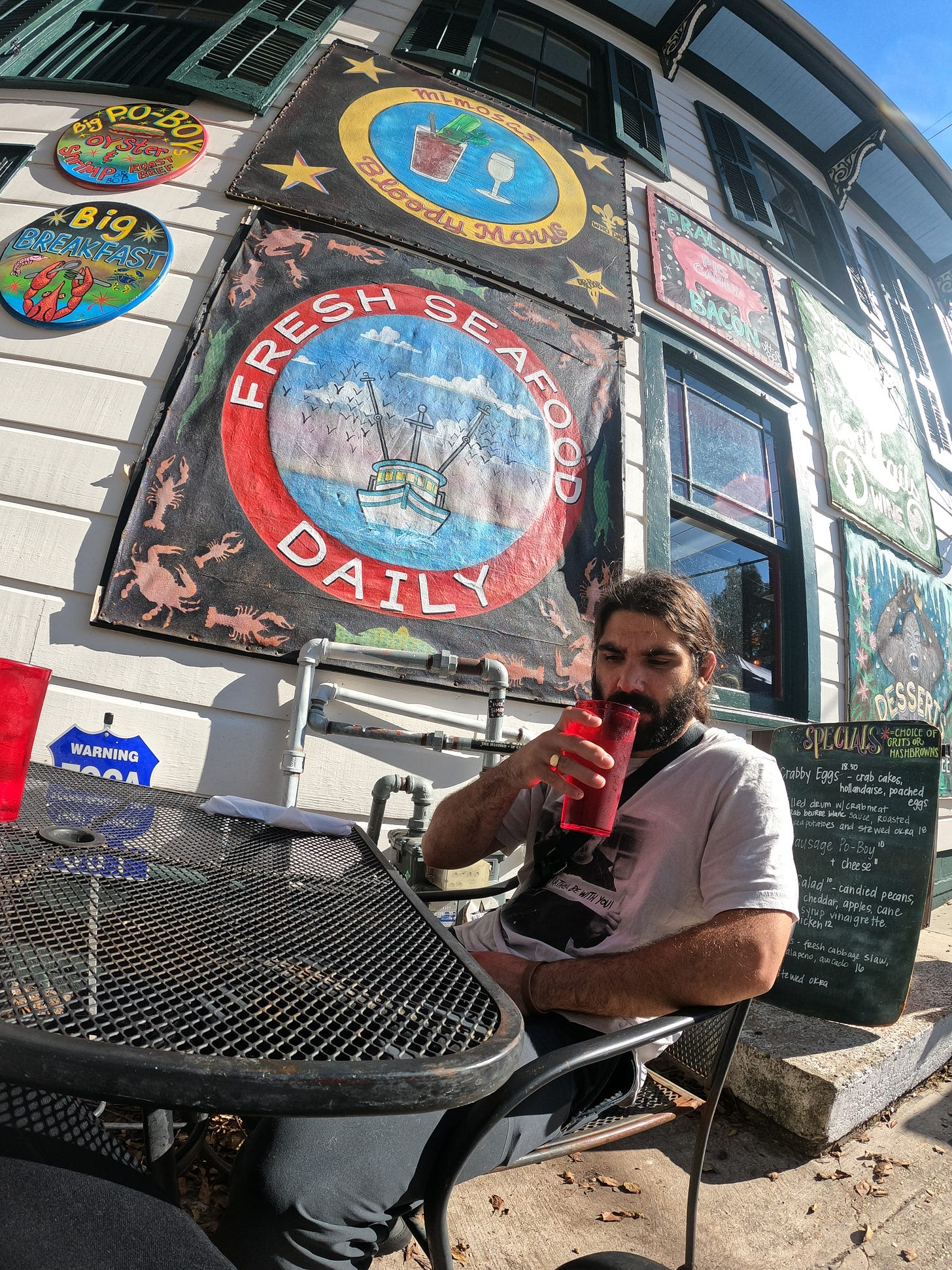 Anthony sipping on his drink sitting in the hot sun outside at Elizabeth's Restaurant