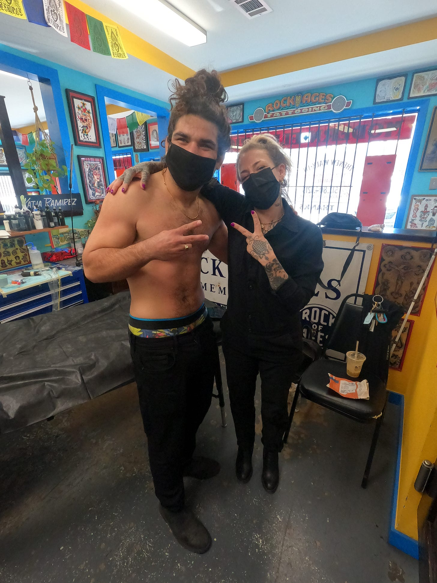 anthony and the tattoo artist hold up peace signs with their hands. Anthony is smiling and has no shirt on