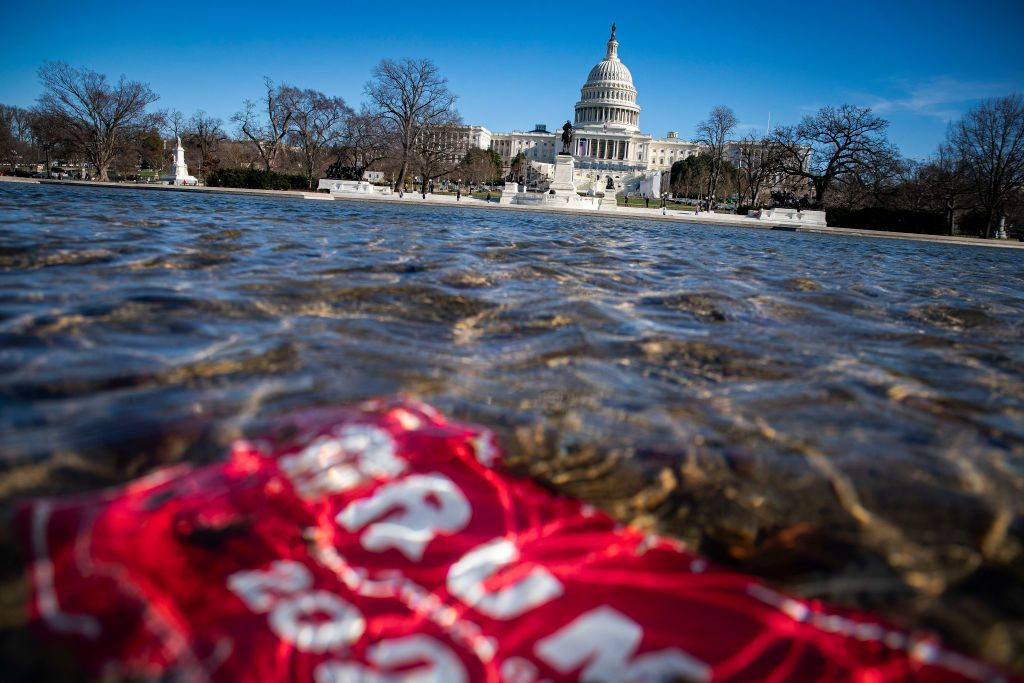 A campaign sign for PresidentTrump lies beneath water in the Capitol Reflecting Pool on Saturday in Washington, DC. (Al Drago/Getty Images)