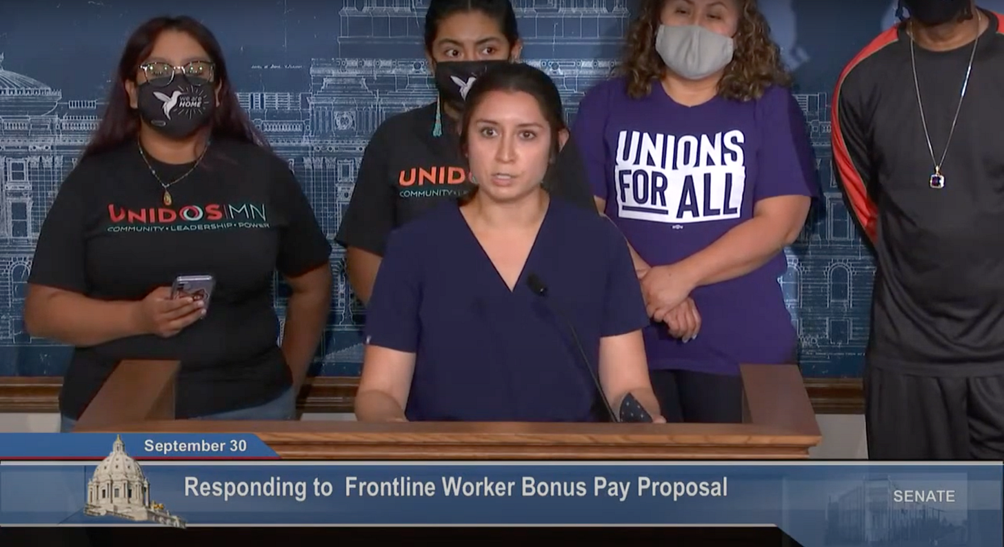A white woman with brown hair in navy scrubs stands behind a podium, behind her people in graphic tees reading Unidos MN and Union for All