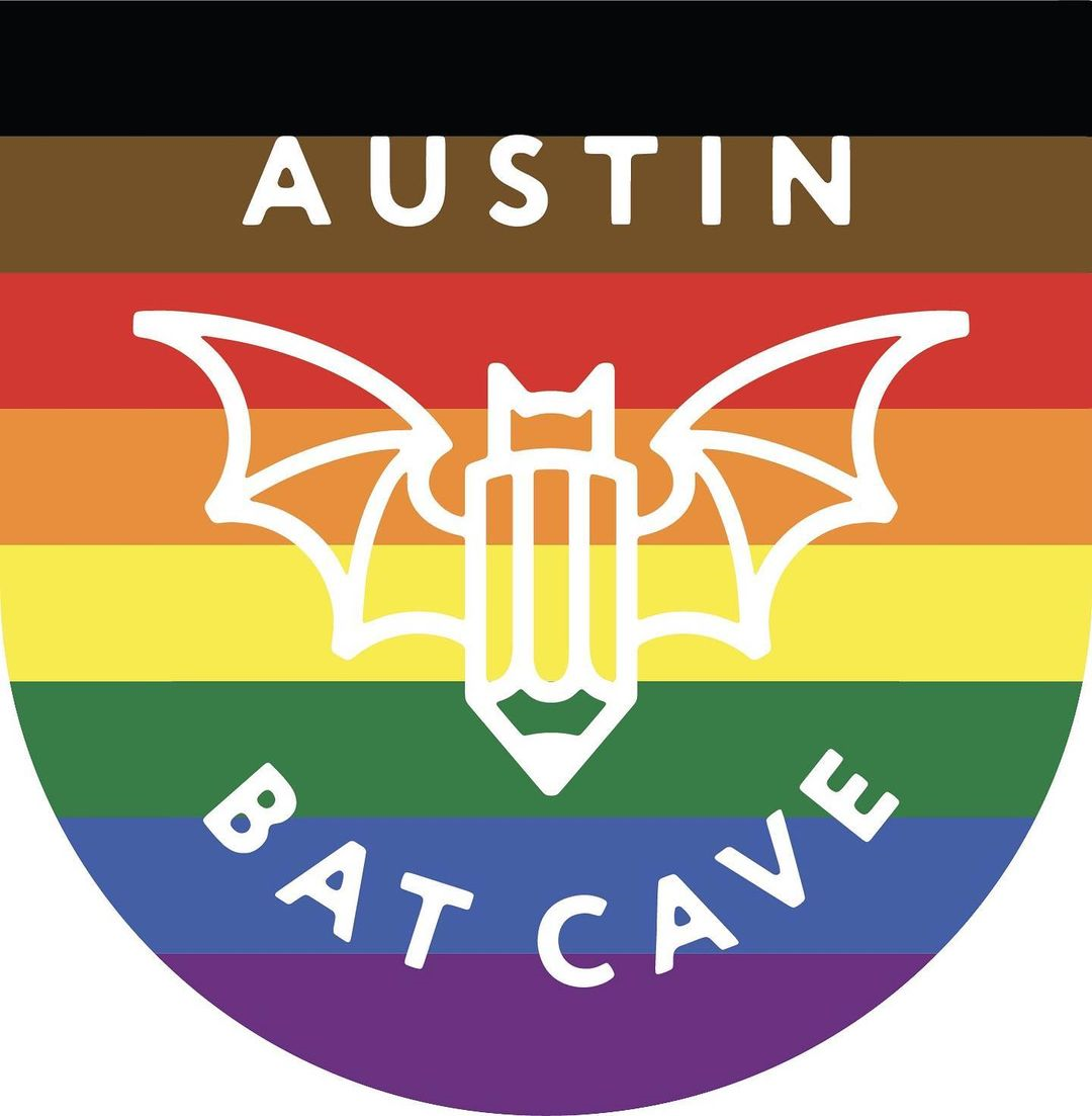 The Austin Bat Cave logo, a bat with the body of a pencil, lays atop black, brown, red, orange, yellow, green, blue, and purple stripes to celebrate Pride.