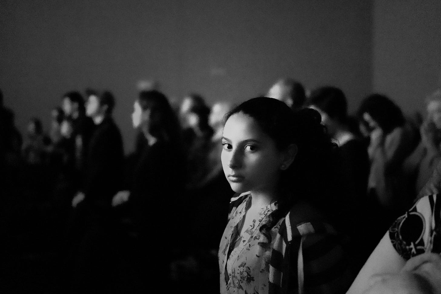 black and white image of a girl in a crowd looking at the camera for article by Larry G. Maguire