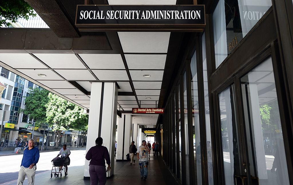 People walk on the street outside a Social Security Administration office, indicated by a large sign above the street, on a sunny day.