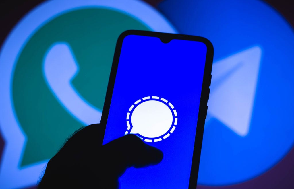 Photo illustration of Signal against a backdrop of WhatsApp and Telegram app icons. (Rafael Henrique / Getty Images)