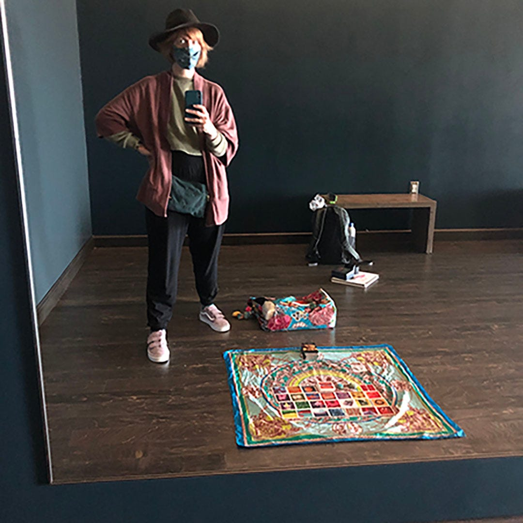 A photo of ilyse taking a picture of herself in the mirror including a full spread of cards on a scarf on a wooden floor in the SFO Yoga Room.