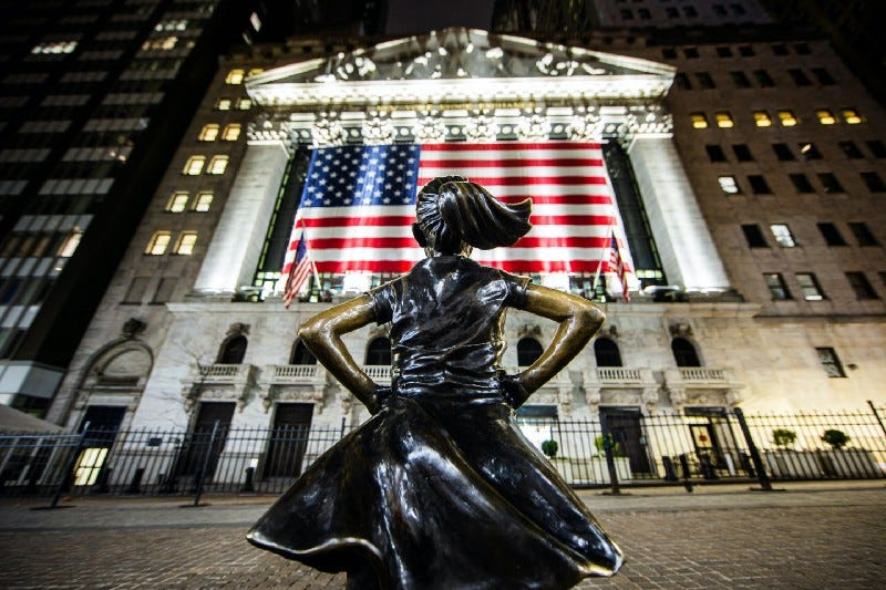 A statue of a girl with her hands on her hips, facing an American flag draping from the New York Stock Exchange.