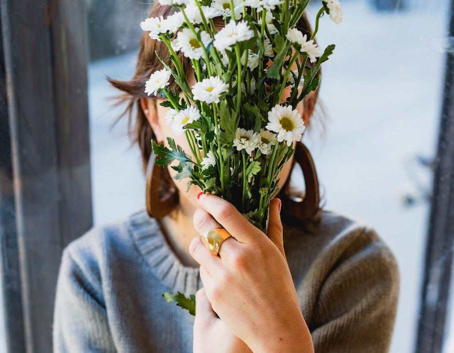 Lady hiding her face behind flowers