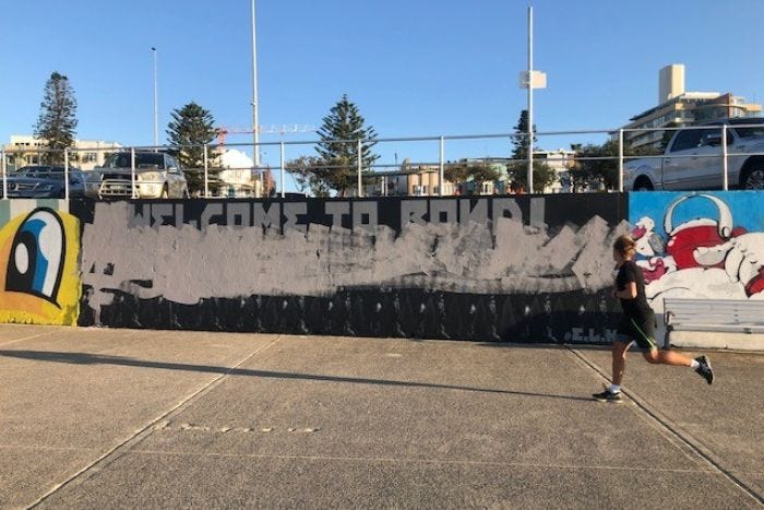 A jogger runs past the vandalised mural.
