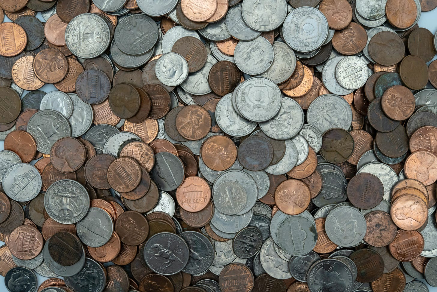 A pile of pennies, nickels, dimes, and quarters, photographed from above.