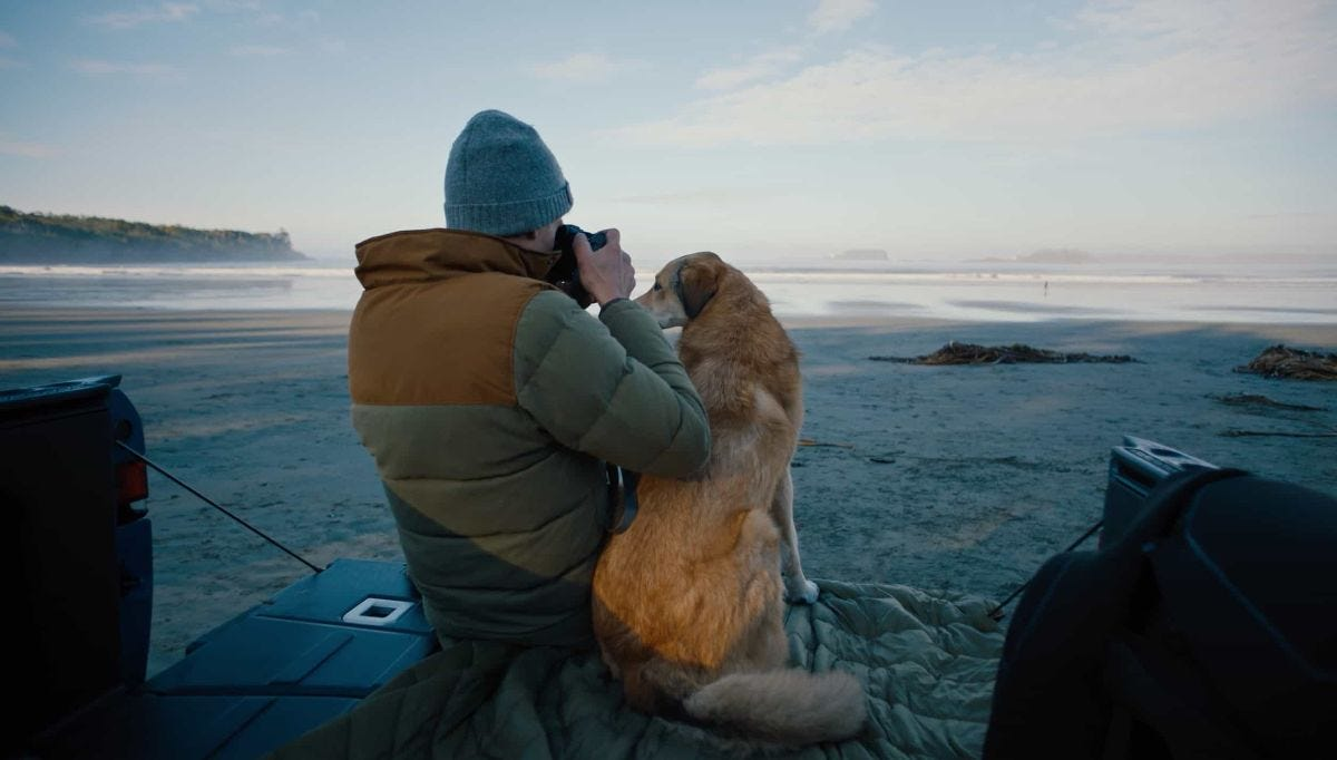ben moon shoots a photo of the ocean from the bed of a truck with his dog by his side