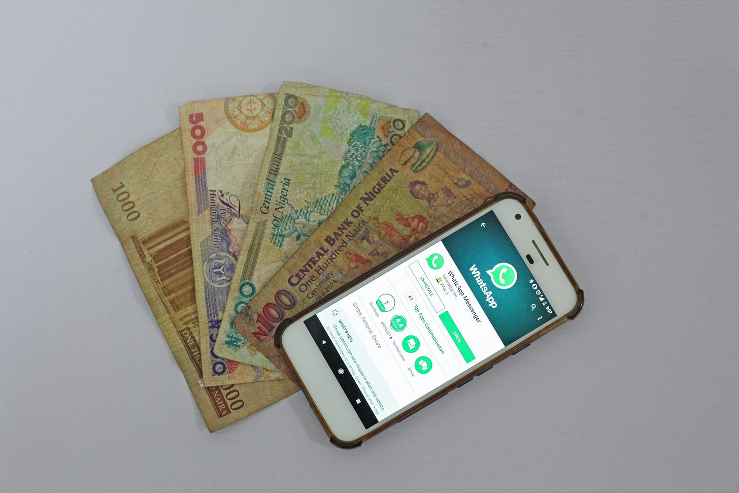 Photo of a phone with WhatsApp open laid on top of currency fanned out underneath it. Benjamin Dada / Unsplash