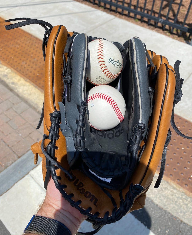 Two baseball gloves, child's nestled inside an adult's, cradling two baseballs.
