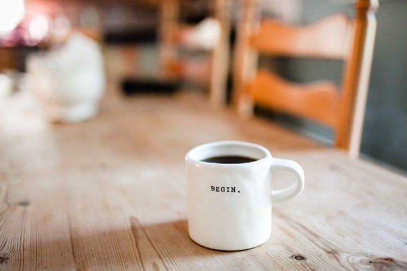 image of a white coffee mug with the word begin written on it, on a table