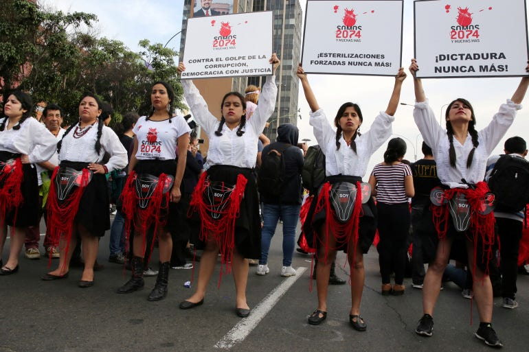 Women hold signs reading 'We are 2,074 and more, forced sterilisations never again' during a protest against violence against women in Lima, Peru, in 2017 [File: Mariana Bazo/Reuters]