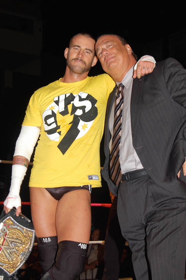 CM Punk and Paul Heyman pose together, smiling