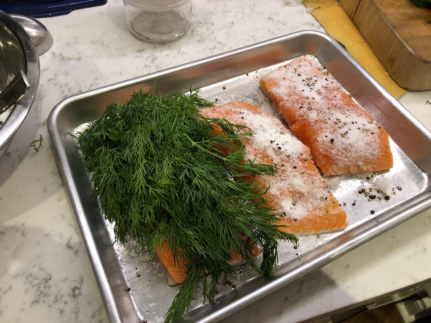 The salmon pieces, covered in the cure. One piece also has a large pile of dill on it, covering it completely.