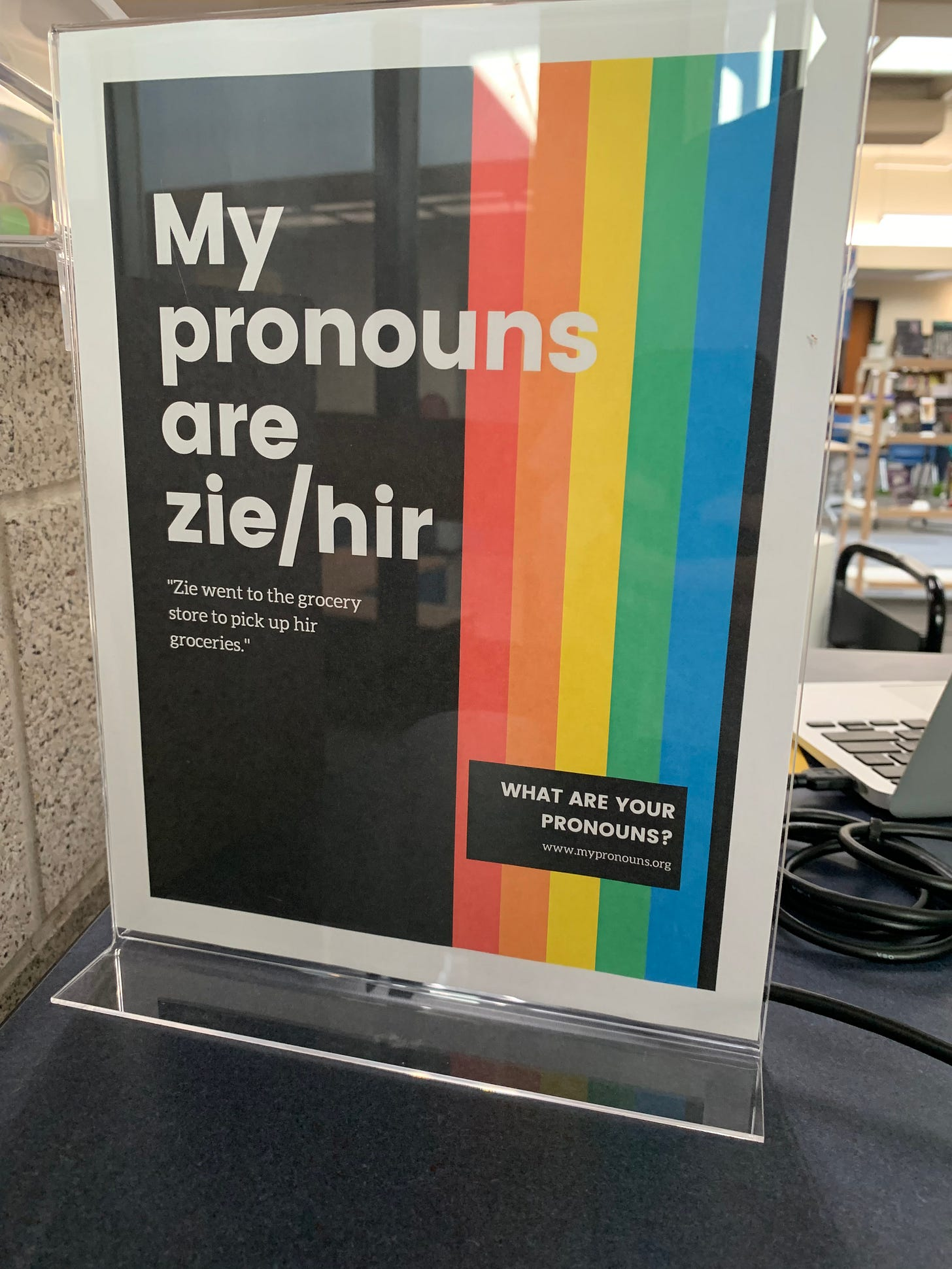 """A poster in a plastic cover has a rainbow over black. The white text reads """"My pronouns are zie/hir. """"Zie went to the grocery store to pick up hir groceries."""" What are you pronouns? www.mypronouns.org"""""""